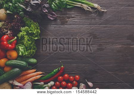 Left side border of fresh organic vegetables on wood background. Healthy natural food on rustic wooden table with copy space. Italian cuisine cooking ingredients top view, soft toning, filtered