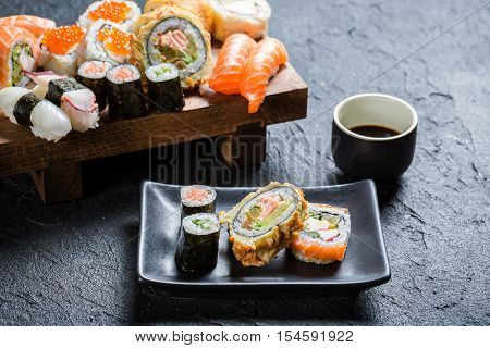 Sushi Served With Soy Sauce On Black Stone