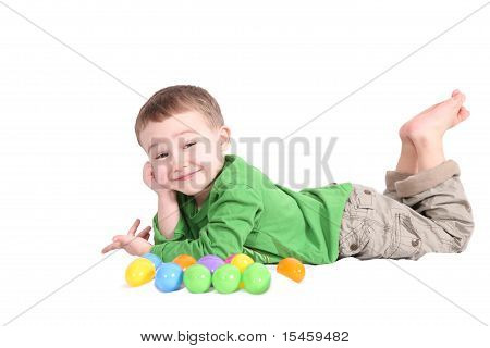 adorable little boy lying with Easter eggs isolated on white