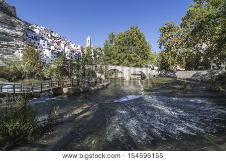 Alcala del Jucar Spain - October 29 2016: Small wooden bridge over the river Jucar located in the central part of the town the fund for the Church of San Andres styles late Gothic and Neoclassic take in Alcala of the Jucar Albacete province Spain
