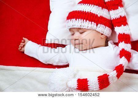 Sleepy baby on red blanket in knitted hat. Cute child sleeping in christmas cap
