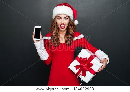 Excited cheerful woman in red santa claus outfit showing blank screen mobile phone and holding present box over black background