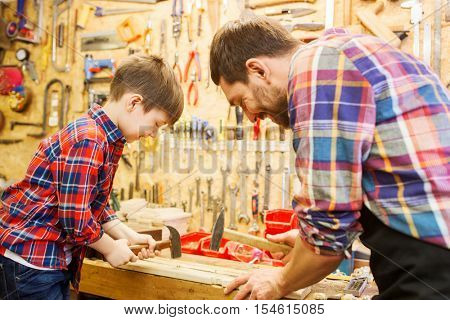 family, carpentry, woodwork and people concept - father and little son with hammer hammering nail into wood plank at workshop