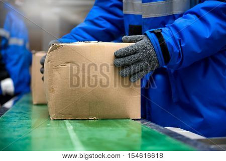 Picking up package boxes from conveyor belt in warehouse or loading area.