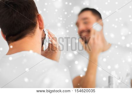 beauty, shaving, grooming and people concept - close up of man applying shaving foam to face and looking to mirror at home bathroom over snow