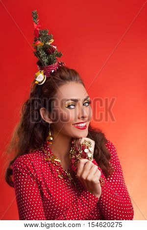 New Year's and Christmas efforts and preparations. Smiling Girl with New Year tree instead of santa hat on head thinks about winter holidays celebration. Woman arranging decorations of Xmas tree. Creative fun studio photo.