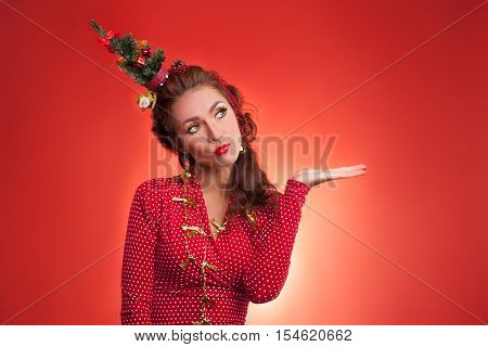 New Year's and Christmas efforts and preparations. Girl with New Year tree instead of santa hat on head thinks about winter holidays celebration holding hand against blank red background. Woman arranging decorations of Xmas tree. Creative fun studio photo