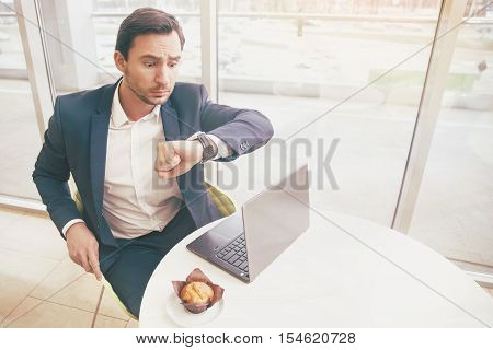 Hurry up. Young elegant punctual businessman in classic costume looking at his watches with surprise while working on a laptop and sitting in an office.