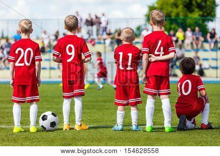 Football soccer match for children. Young boys of football soccer team watching youth football game on sports field. Kids playing summer school football tournament