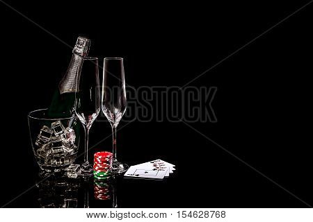 Bottle of champagne in an ice bucket with two wineglasses and cards and colorful chips