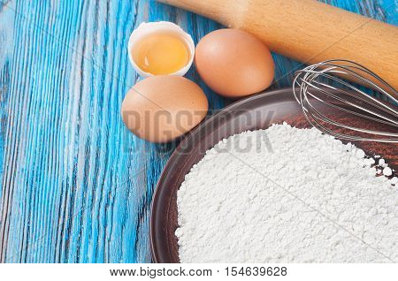 Eggs egg yolk and flour on a blue wooden background