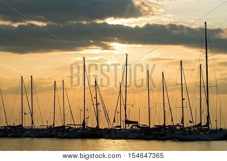 Silhouettes of masts at sunset at the seafront of Thessaloniki Greece