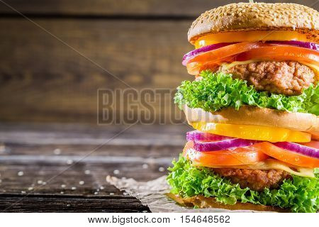 Closeup of homemade double-decker burger on old wooden table