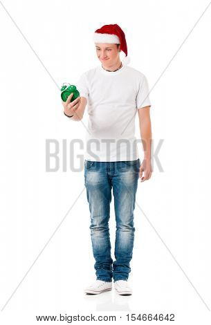 Caucasian young man wearing christmas hat for santa. Teenager in white t-shirt with alarm clock isolated on white background. Happy boy wearing Santa Claus hat - full length portrait.