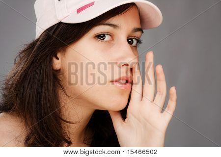 pretty teen girl whispering, studio shot