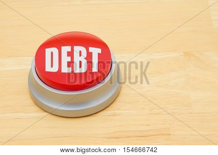 A Debt red push button A red and silver push button on a wooden desk with text Debt