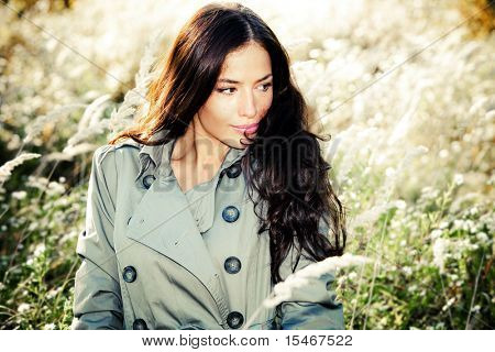 young woman in topcoat walking accros the autumn meadow, sunny autumn day