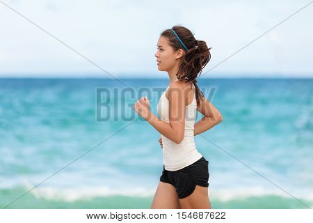 Fit sport athlete running woman runner jogging on outdoor workout on beach. Asian young woman running outdoors training for marathon run. Beautiful fit fitness model in her 20s.