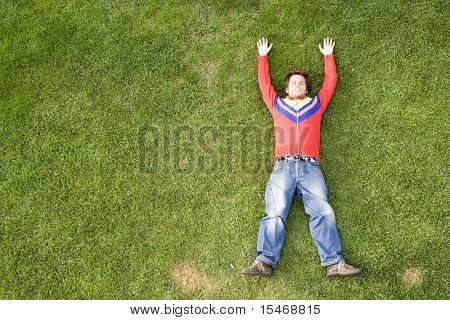 a young man lay down on the grass with plenty copy space