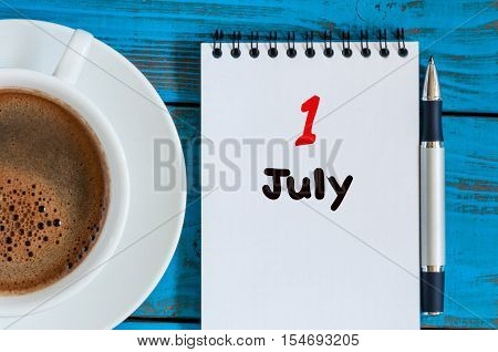 July 1st. Day of the month 1 , calendar on business workplace background with morning coffee cup. Summer concept. Empty space for text.