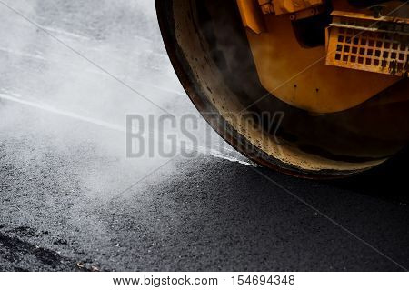 Asphalt paving with a steel wheel roller. Steam coming out from asphalt.