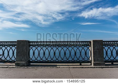 Wrought iron railings with concrete pillars against the blue sky with clouds. Symmetry, background, concept