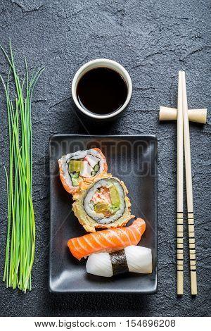 Fresh sushi dark ceramic and chopstick on black rock