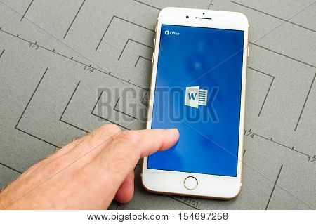 PARIS FRANCE - SEPT 26 2016: New iPhone 7 Plus with hand touching screen to make a new Microsoft Word document on mobile phone. iPhone 7 and iPhone 7 plus is the most wanted phone worldwide