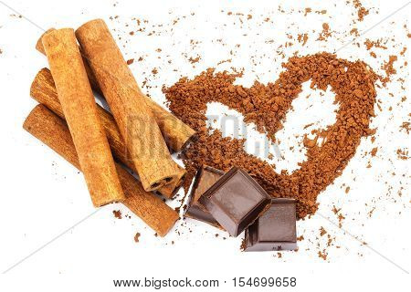 Cinnamon sticks chocolate cubes and cacao powder in shape of heart isolated on white background top view close-up