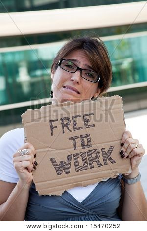 unemployed woman showing a message in a cardboard that she is free to work