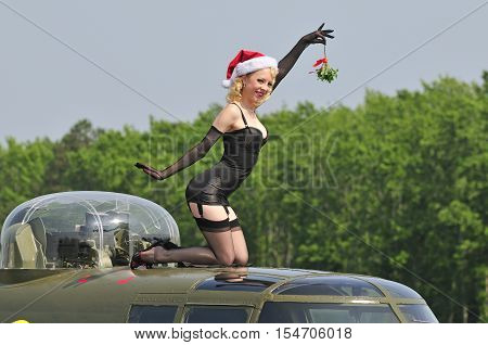 Sexy pinup vixen holding up a mistletoe while sitting on top of a WWII bomber aircraft
