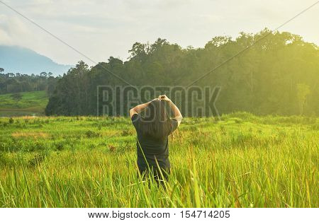 Beautiful long hair girl stands in the green grass field under rim light. A woman in black cloth is standing in the grass field.