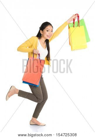 Happy young Asian woman shopper running, hands outstretched holding shopping bags and smiling, full length isolated standing on white background.
