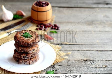 A stack of fried bean patties on a plate. Delicious vegetarian patties cooked from boiled red beans. Old wooden background with blank copy space for text. Vintage style