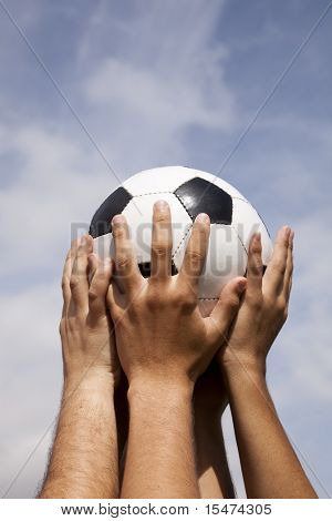 Soccer team raising a ball to the sky