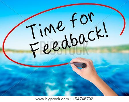 Woman Hand Writing Time For Feedback With A Marker Over Transparent Board