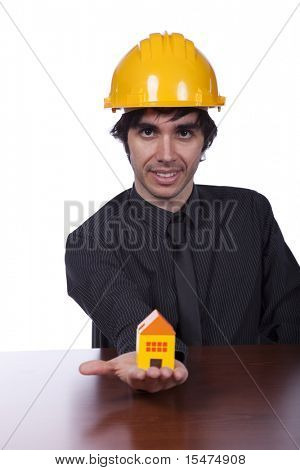 young construction engineer showing you a small yellow house