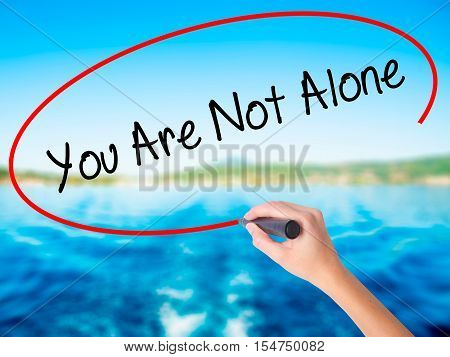 Woman Hand Writing  You Are Not Alone With A Marker Over Transparent Board