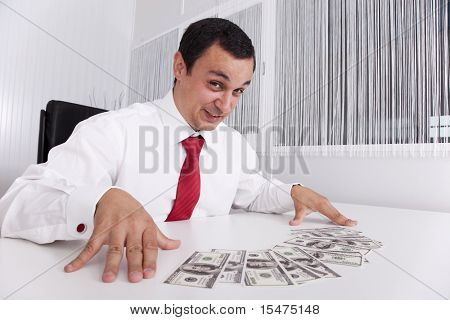 Businessman at the office enjoying his money