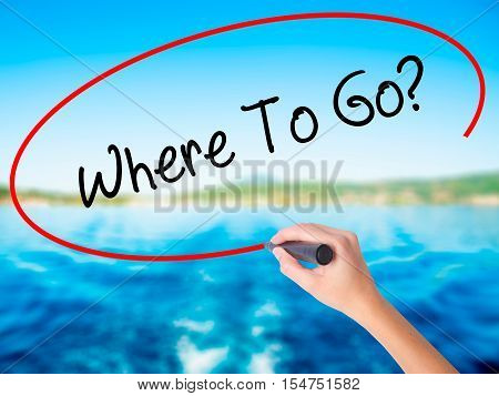 Woman Hand Writing Where To Go? With A Marker Over Transparent Board