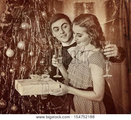 Retro vintage portrait of couple on party near Christmas tree. Couple drink champagne. Girl keep gift box. Black and white retro on yellow paper.