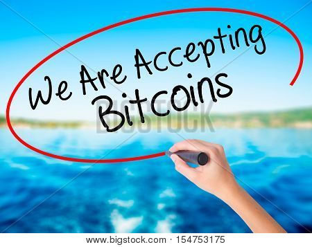 Woman Hand Writing We Are Accepting Bitcoins With A Marker Over Transparent Board