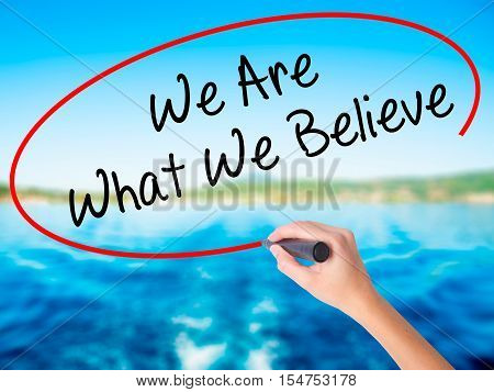 Woman Hand Writing We Are What We Believe With A Marker Over Transparent Board