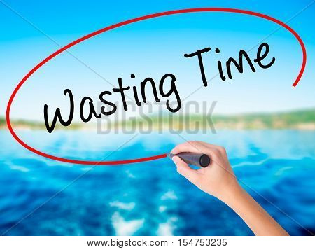 Woman Hand Writing Wasting Time With A Marker Over Transparent Board