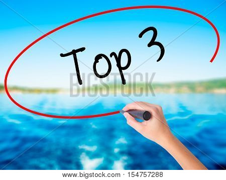 Woman Hand Writing Top 3 With A Marker Over Transparent Board