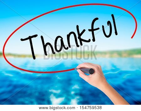 Woman Hand Writing Thankful  With A Marker Over Transparent Board