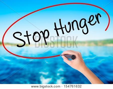 Woman Hand Writing  Stop Hunger With A Marker Over Transparent Board
