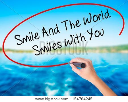 Woman Hand Writing Smile And The World Smiles To You With A Marker Over Transparent Board
