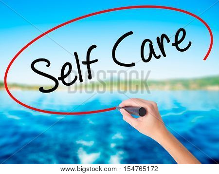 Woman Hand Writing Self Care With A Marker Over Transparent Board