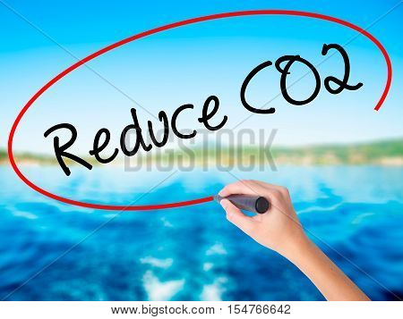 Woman Hand Writing Reduce Co2 With A Marker Over Transparent Board.